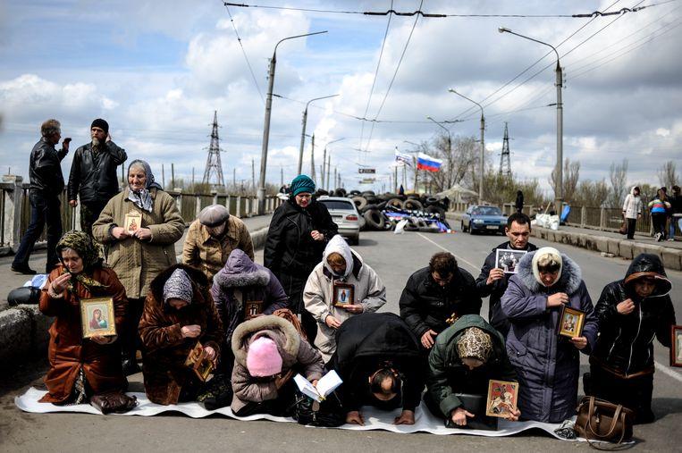 Vrouwen bidden voor vrede voor het regionale regeringsgebouw in Slovjansk, Oost-Oekraïne. Beeld AP