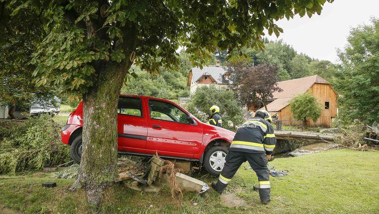Brandweerlui in Kobenz (Oostenrijk) zijn druk in de weer om een wagen op te ruimen die door een modderstroom was meegesleurd. Beeld afp