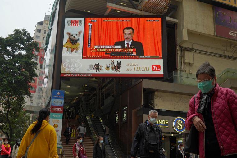 De openingssessie van het Nationale Volkscongres is vrijdag te zien op straat in Hongkong.  Beeld AP