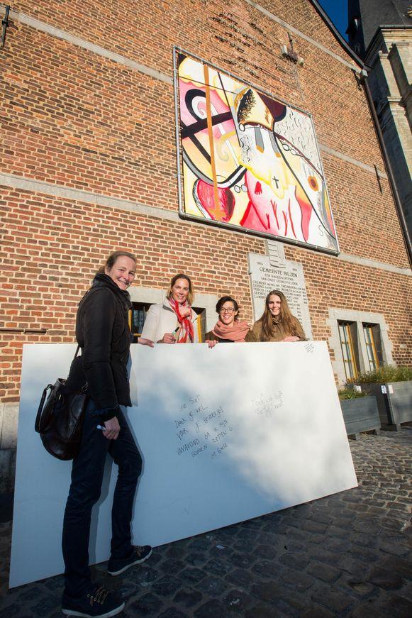 Schepen Griet Mebis met de drie leerkrachten van de Kunstkoepel bij het kunstwerk.