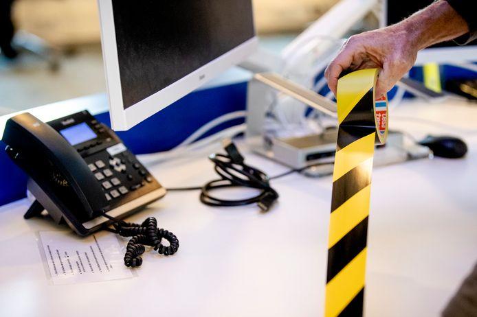 Foto ter illustratie. Een werkplek wordt afgezet met tape om 1,5 meter afstand te kunnen bewaren.