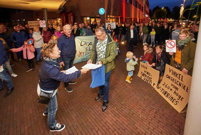 Protest bij gemeentehuis Heesch tegen windmolens, raadsleden krijgen flyers in handen gedrukt voordat ze het gemeentehuis in gaan.