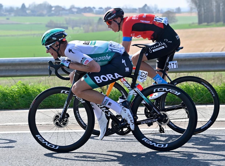 De Duitser Nils Politt daalt op de buis tijdens Dwars door Vlaanderen. Dylan Teuns neemt een klassieke fietshouding aan. Beeld Photo News