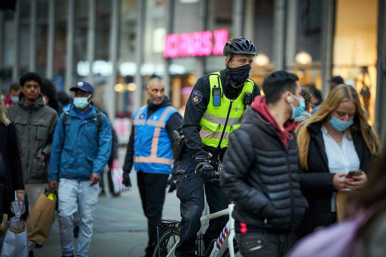 Politie en winkelend publiek in de Koopgoot in Rotterdam. Beeld ANP