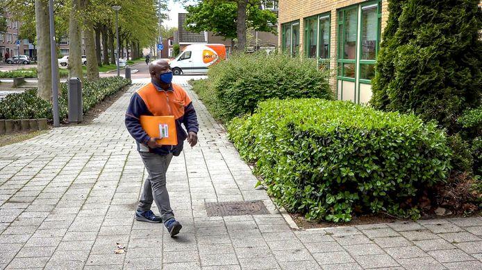 Een bezorger van PostNL levert het examen in een speciale oranje envelop af op de school