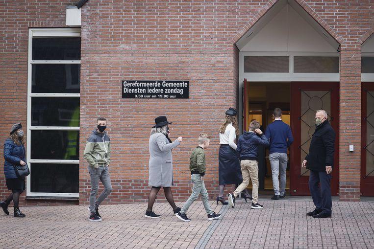 Kerkgangers komen aan bij de Rehobothkerk voor de wekelijkse kerkdienst. De Gereformeerde Gemeente Barneveld-Centrum laat meer dan dertig bezoekers per dienst toe. Beeld ANP