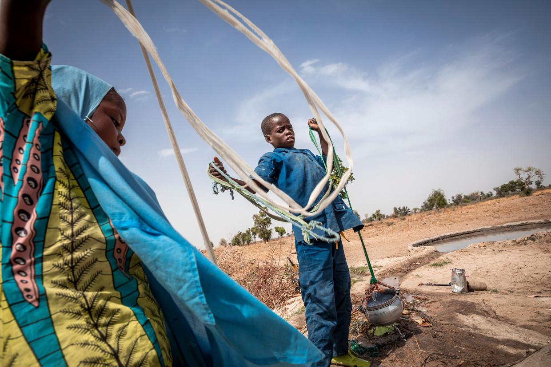 Kinderen halen water uit een zelf gegraven put in het kamp in Mémé, waar ontheemde Kameroeners en vluchtelingen uit Nigeria zijn neergestreken. Beeld