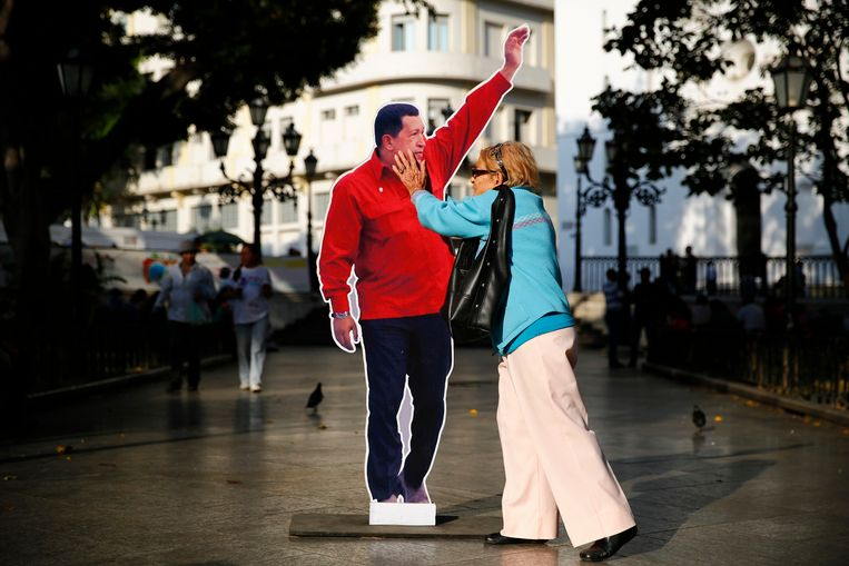 A woman touches a cardboard cut-out of late Venezuela's president Hugo Chavez at Plaza Bolivar in Caracas March 9, 2014. Followers of Chavez are commemorating the first anniversary of his death this week, a sad but welcome distraction for his successor who has faced a month of violent protests. A year after Chavez succumbed to cancer, his self-proclaimed 'son,' President Nicolas Maduro, faces the biggest challenge to his rule from a month-long explosion of anti-government demonstrations that have led to 20 deaths. REUTERS/Jorge Silva (VENEZUELA - Tags: POLITICS ANNIVERSARY TPX IMAGES OF THE DAY) Beeld REUTERS
