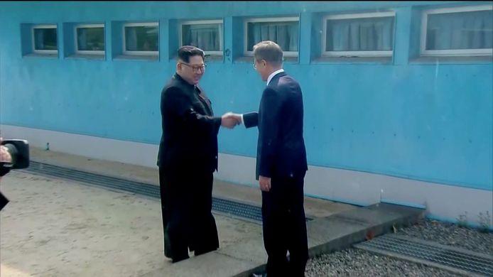 De Noord-Koreaanse leider Kim Jong-un en zijn Zuid-Koreaanse ambtsgenoot Moon Jae-in schudden elkaar de hand in het dorpje Panmunjom, hier nog elk aan hun kant van de grens.