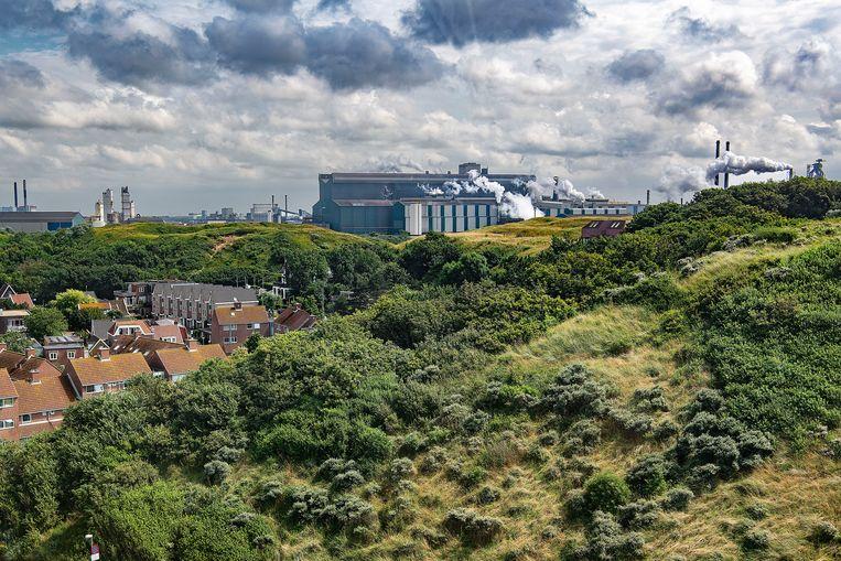 Het stadje Wijk aan Zee, links, met in de achtergrond Tata Steel. Omwonenden zijn een actie gestart om zelf de schadelijkheid van de uitstootgassen van de staalfabrikant te onderzoeken.  Beeld Guus Dubbeldam/Volkskrant