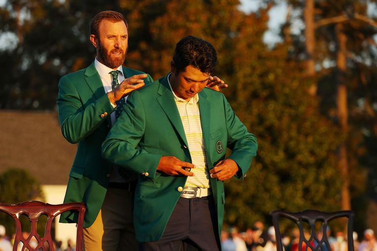 Golfer Hedeki Matsuyama neemt het groene jasje in ontvangst. Beeld AFP