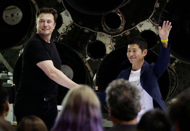 De Japanse miljardair Yusaku Maezawa (rechts) schudt de hand van SpaceX-oprichter Elon Musk. Beeld AP