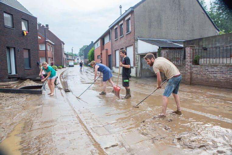 Buren sloegen in Asse de handen in elkaar om met vereende krachten de straat zo snel mogelijk vrij te krijgen na wateroverlast. Beeld Tom Vierendeels