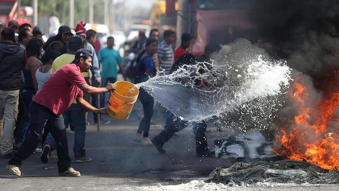 Een man probeert een brandje te blussen bij protesten in San Miguel Totolcingo.