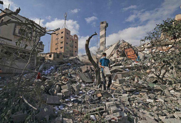 Een Palestijnse jongere zoekt nog bruikbare spullen tussen het puin, in Gaza-stad. Beeld AFP