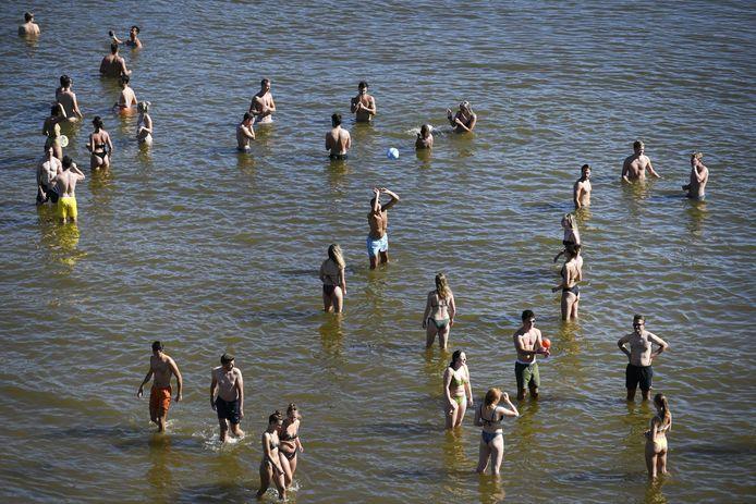 Mensen koelen - veelal op veilige afstand - af in het water.