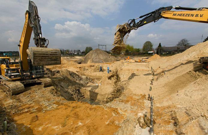 Vervuilde grond eruit (links), schone grond erin (rechts) op het voormalige terrein van machinefabriek Te Strake in Deurne.