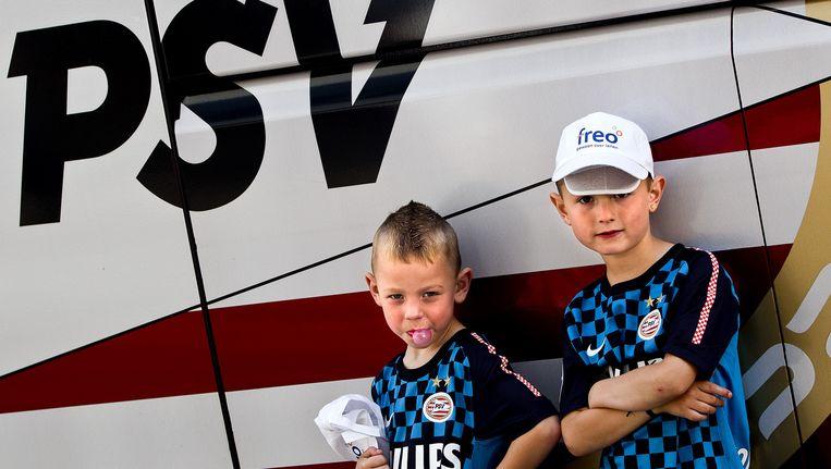 Twee jonge supporters poseren bij de spelersbus van PSV. Beeld anp