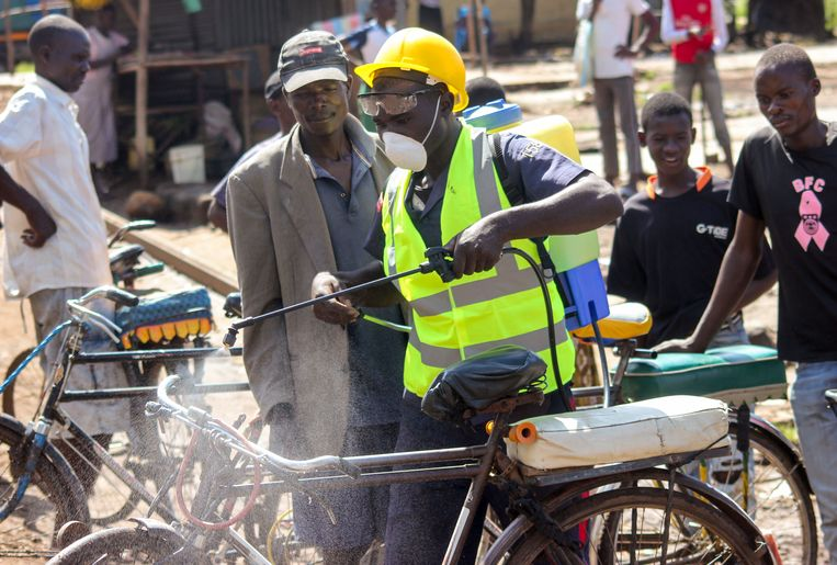 De berijder desinfecteert zijn fietstaxi bij een markt in Kisumu, in het westen van Kenia. Het land ontkomt niet aan de coronapandemie, al valt de besmetingsgraad er relatief mee. Beeld AP