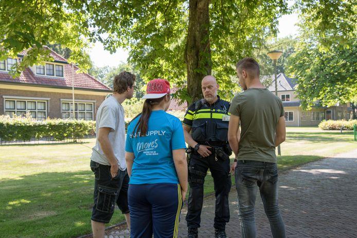Wijkagent Jurion Veenstra in gesprek met jongeren op het terrein van Groot Emaus.
