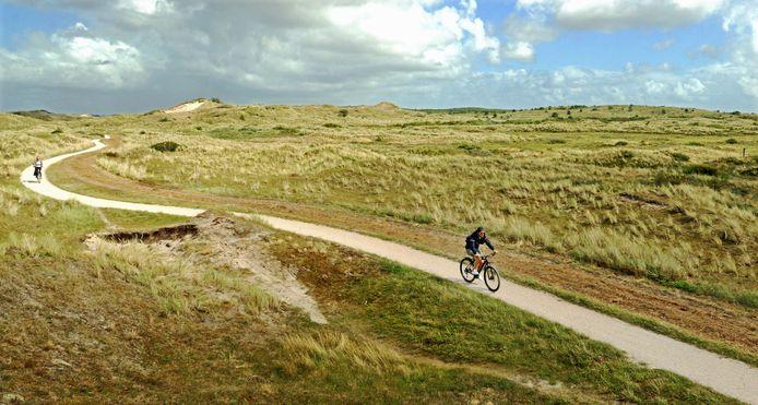 Fietsers op een pad door de duinen aan de noordkust van Vlieland.