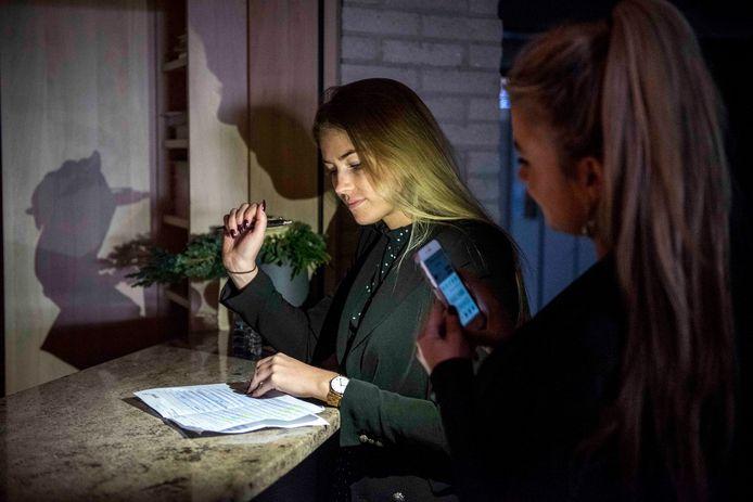 Medewerkers Desi Skacokova en Leni Basista checken met een zaklamp de lijst van bezoekers in het Strandhotel.