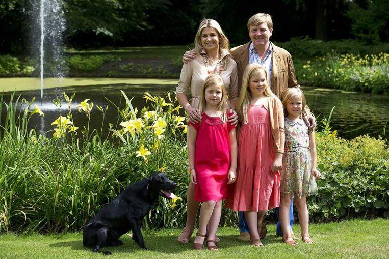 oning Willem-Alexander en koningin Maxima met de prinsesjes Amalia (m), Alexia (l) en Ariane (r) poseren met de labrador Skipper tijdens de traditionele fotosessie op landgoed De Horsten in Wassenaar. Beeld anp