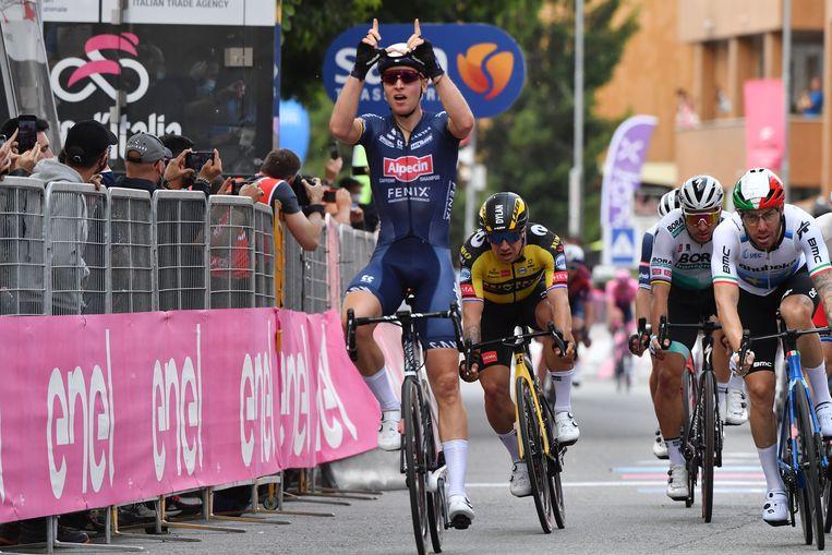 Tim Merlier maakt met zijn handen een W, als eerbetoon aan Wouter Weylandt. Hij won de sprint in Novara voor onder anderen Nizzolo (r.) en Groenewegen. Beeld REUTERS