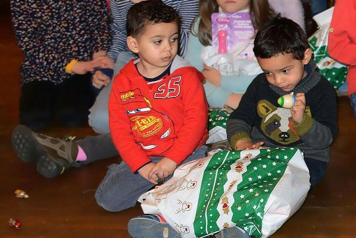 Twee kinderen openen hun geschenkje.