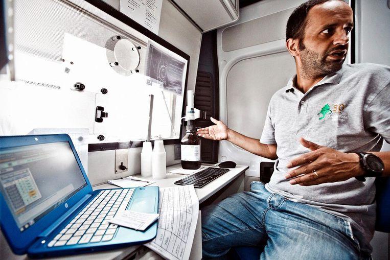 Verpleger Rafael Monteiro dient een dosis methadon toe aan een gebruiker in de methadonbus. Beeld Jonas Lampens