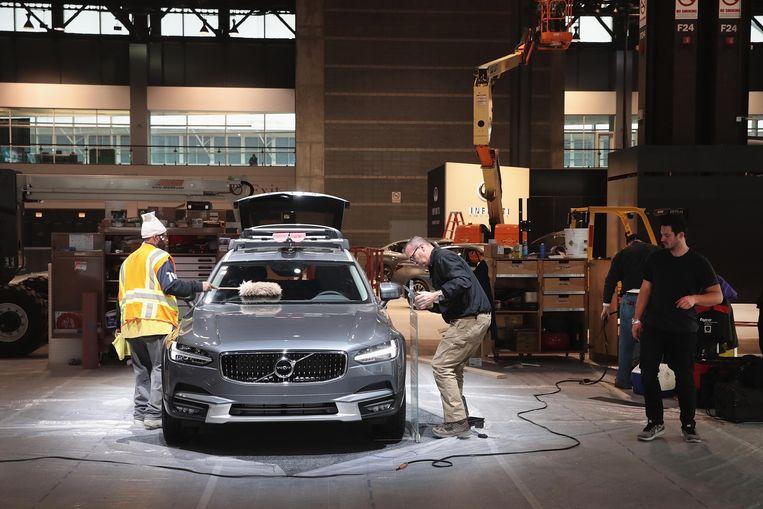 Een Volvo V90 Cross Country wordt klaargezet op de stand in aanbouw voor de autobeurs van Chicago in 2019.  Beeld AFP