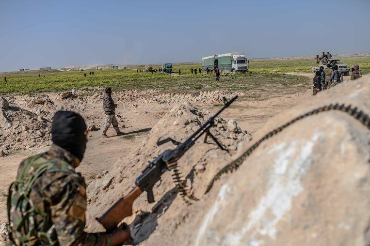 Strijdkrachten van de Syrische Democratische Strijdkrachten voeren IS-strijders af in Baghouz in Syrië.  Beeld AFP