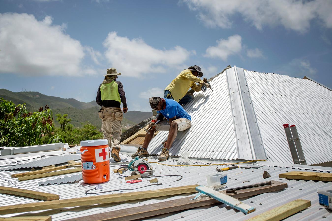 Een bouwteam van het Rode Kruis repareert een dak in de wijk Dutch Quarter.