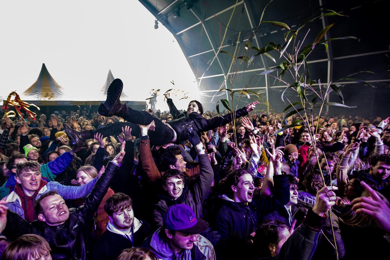 Een crowdsurfende bezoeker tijdens een optreden van de Nederlandse rockband De Staat op popfestival Back To Live in Biddinghuizen, afgelopen maart. Het evenement valt onder een reeks van proefevenementen waarbij Fieldlab onderzoekt hoe grote evenementen veilig kunnen plaatsvinden in coronatijd.