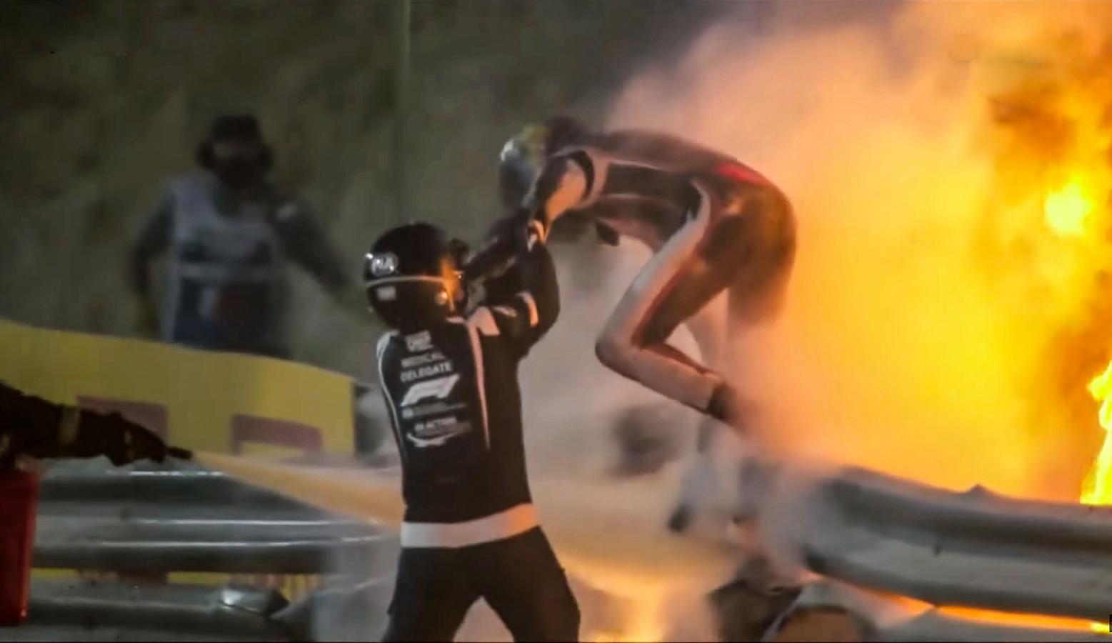 Romain Grosjean verlaat zijn zojuist in tweeën gebroken Formule 1-auto en ontsnapt uit de ontstane vlammenzee.