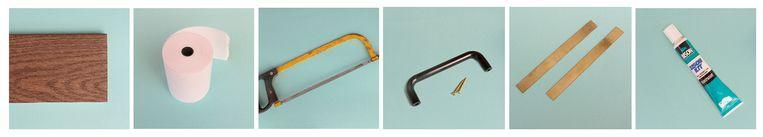 Wat heb je nodig? Plankje (13 x 30 cm) - rolletje papier (8 cm breed) - ijzerzaag - handvat + 2 vijzen - 2 metalen strookjes (13 cm lang) - superlijm Beeld Astrid De Prez