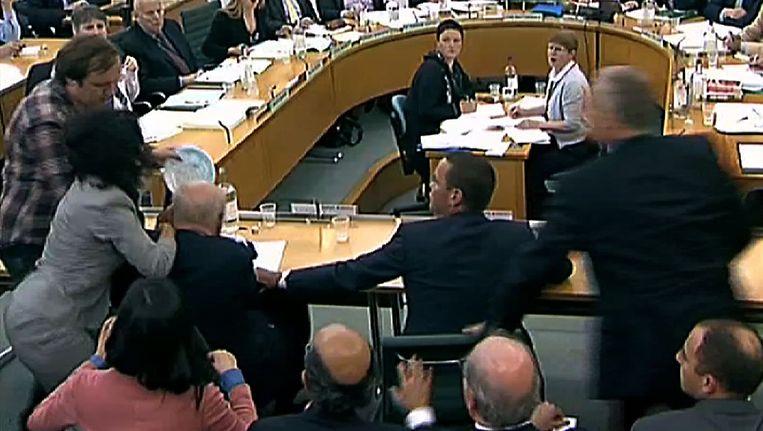 Een man (links) probeert een 'taart' van scheerschuim in het gezicht van Rupert Murdoch te duwen. Beeld AFP
