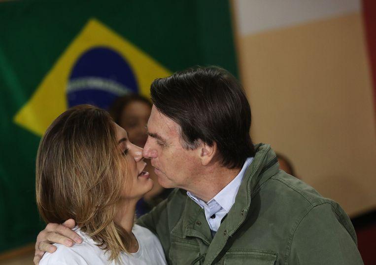 Bolsonaro kust zijn vrouw Michelle voor hij zijn stem gaat uitbrengen in Rio de Janeiro. Beeld AFP