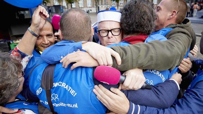 Jan Roos haalt handtekeningen op voor GeenPeil op het Plein in Den Haag. Met een groepsknuffel bedankt hij de vrijwilligers.