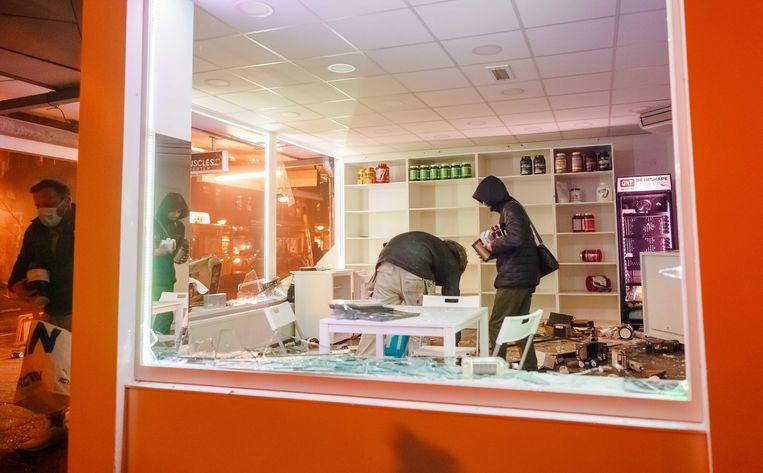 Plunderingen in een winkel in Rotterdam.  Beeld ANP