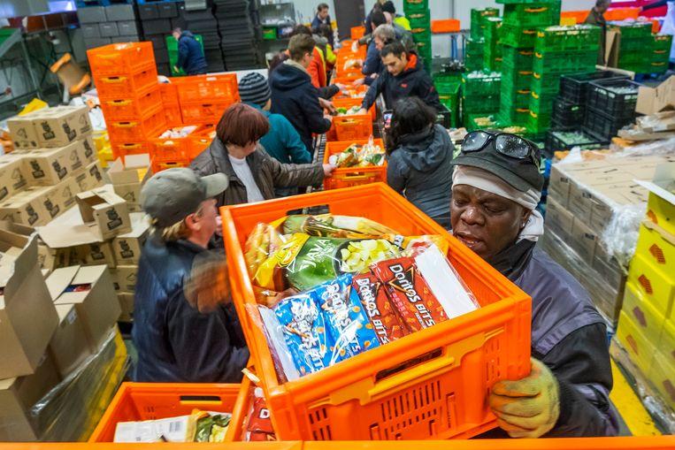 Vrijwilligers, werkelozen en verstandelijk gehandicapten aan het werk bij de voedselbank in Rotterdam-West, waar de vraag is toegenomen.  Beeld Hollandse Hoogte / Hans van Rhoon