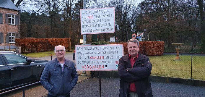 Peter Symens (rechts) van Natuurpunt en buurtbewoner Herman Van Den Heuvel (links) bij het protestbord met in de achtergrond het domein waar de schietstand zou komen.
