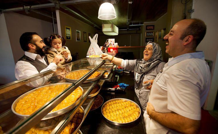 Mensen kopen zoete lekkernijen in een bakkerij in Rotterdam op de eerste dag van het offerfeest. Beeld Hollandse Hoogte / ANP