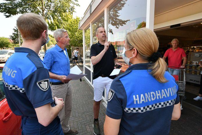 Supermarkteigenaar Raymond Berning weigerde de brief aan te nemen die Ton Kamp (blauwe blouse) hem namens de veiligheidsregio kwam overhandigen
