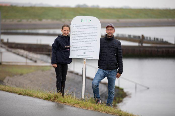 Vos Broekema met dochter Zorra bij de grafzerk die hij maakte voor de gesneuvelde bloemen op de Oosterscheldedijk bij de Heerenkeet.
