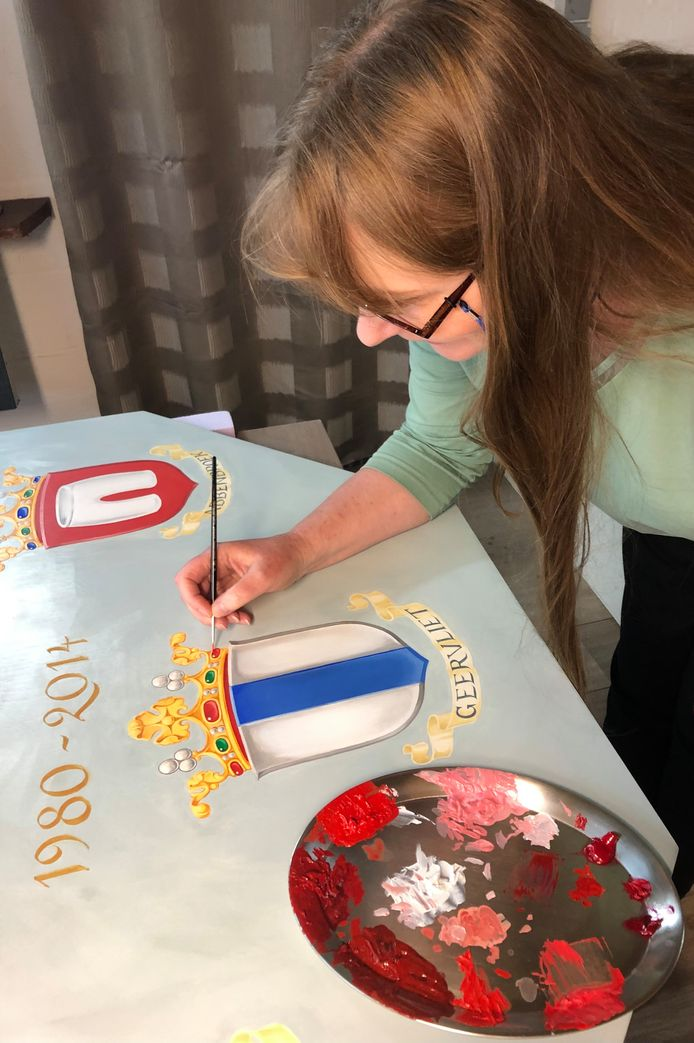 Prisca van Dessel, de heraldisch tekenaar uit België, legt de laatste hand aan de markiezenkroon van het gemeentewapen van Geervliet op het wapenbord van Bernisse.