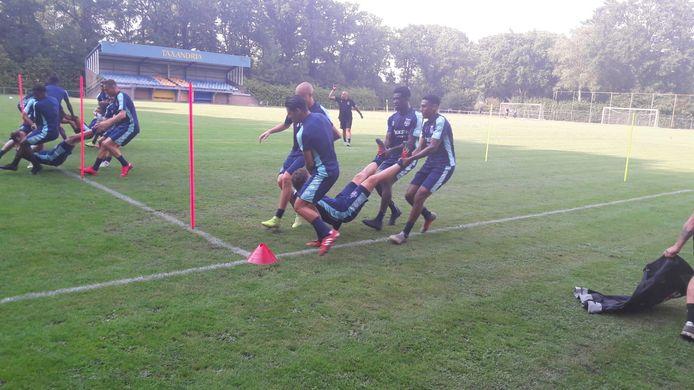 Een speelse trainingsopdracht, waarbij de spelers van Willem II elkaar tussen de paaltjes door moeten tillen.