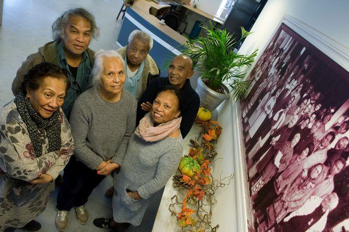 Zes Molukkers van de tweede generatie uit Tiel bij een foto van hun ouders. V.l.n.r.  vooraan Corrie Merkestein-Tomatala, Tien Leatemia, Josefien Talapessy en achteraan Vic Latumahina, Okke Talapessy en Sephus Tahamata.