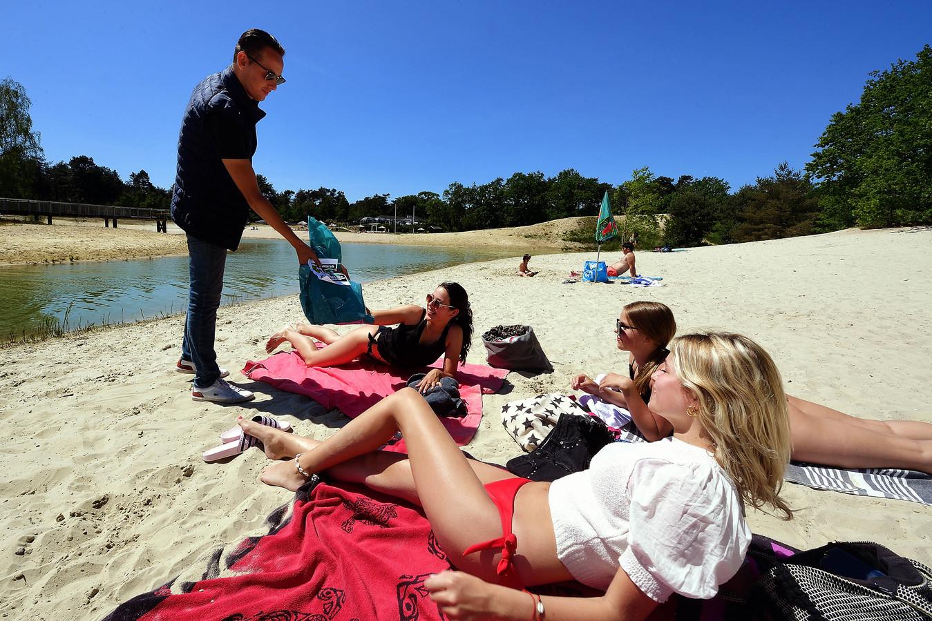 De veertienjarige meiden Zoë Haast, Ilse van Tilburg en Sofie Ruedisueli (vlnr) krijgen een vuilniszak met flyer uitgebreid. Ze erkennen dat er veel troep wordt achtergelaten op het strand bij De Bergse Heide.