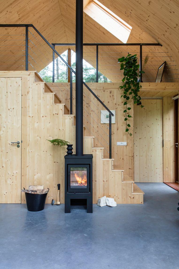 Deze kachel van Buntfires is precies goed voor dit huis, dat geen gasaansluiting heeft. De trap is bedacht door architect Daniël Venneman. In vijf van de treden zitten lades verwerkt.  Beeld Henny van Belkom